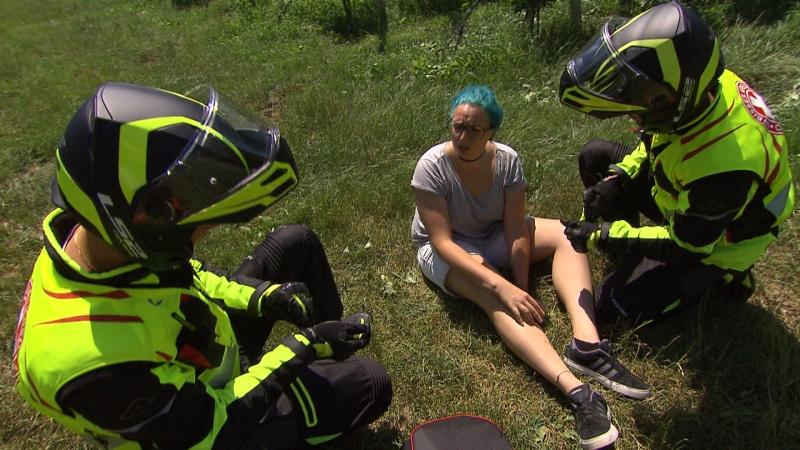 Zwei Motorradsanitäter sprechen mit einer Patientin, die am Boden einer Wiese sitzt (Szene gestellt)