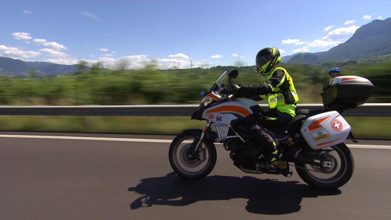 Ein Sanitäter des Weißen Kreuzes mit gelber Warnweste unterwegs auf dem Motorrad