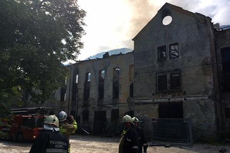 Ausgebrannte Ruine des Brauerei in Koppl-Guggenthal nach dem Großbrand mit Feuerwehrleuten