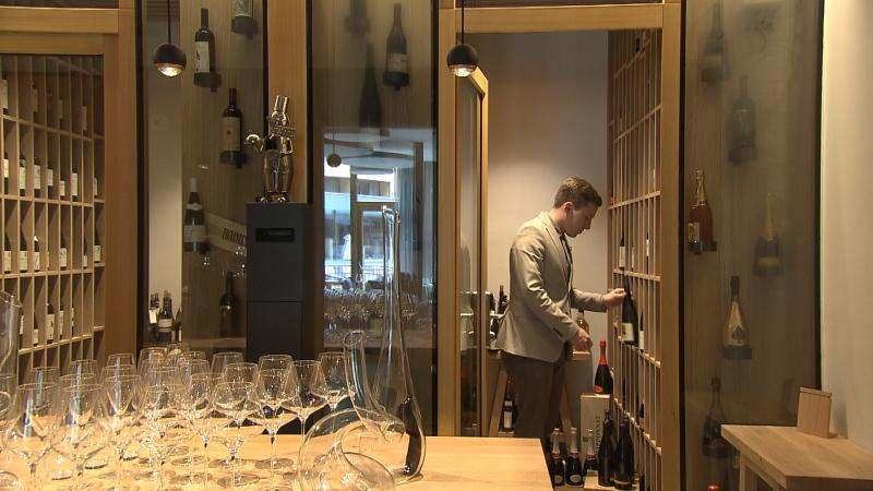 Eros Teboni vor einem Weinregal, im Vordergrund viele leere Weingläser