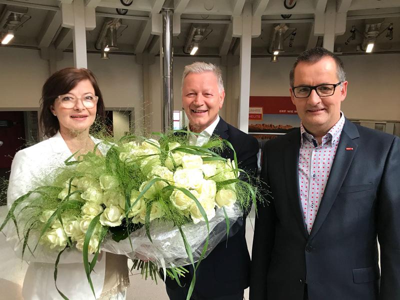 Brigitte Gogl und Helmut Krieghofer mit Blumenstrauß, daneben Robert Unterweger