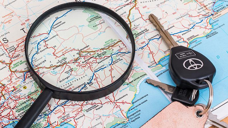 Symbolbild Urlaub Landkarte Lupe Autoschlüssel