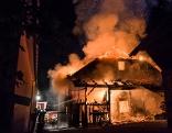 Einsatzkräfte löschen brennendes Haus
