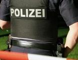 Polizist an Tatort in der Nacht von hinten mit kurzem Hemd und Waffe am Gürtel