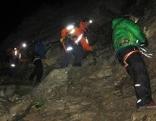 Bergretter bei nächtlichem Sucheinsatz im Hochgebirge im Sommer mit Stirnlampen