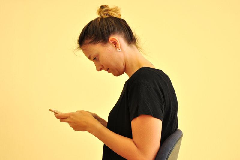 Die Anteflexionshaltung. Die Smartphone-Userin beugt den Kopf um 45 Grad nach vor, um Apps zu nutzen