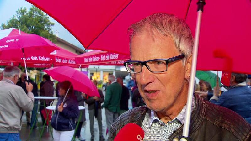 Alois Oberer unter Regenschirm