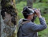 Jäger steht im Wald und sieht durch das Fernrohr.