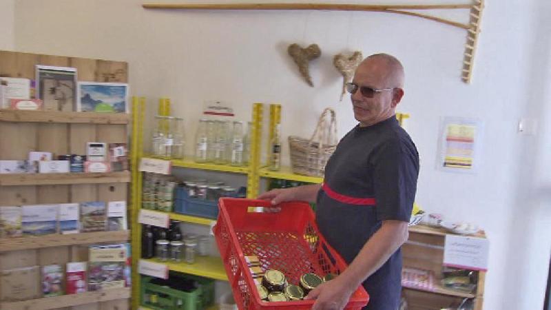 Mann bringt eine Kiste mit Honig ins Geschäft