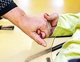 Frau hält Hand einer Pflegebedürftigen