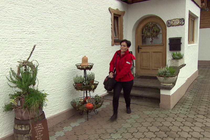 Hauskrankenschwester der Volkshilfe (mobile Pflegerin) vor Haustür - im Laufschritt