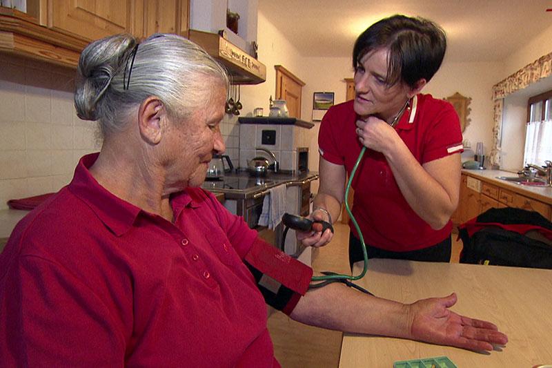 Hauskrankenschwester der Volkshilfe (mobile Pflegerin) bei Klientin beim Blutdruckmessen