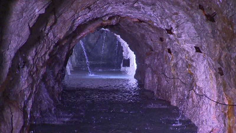 Wasser fließt aus den Felsen in einen Trinkwasserstollen
