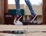 Springende Füße über eine Wasserpfütze