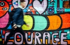 Graffiti und junger Mann davor