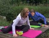 Doresia Krings und Michael Mayrhofer dehnen die Gesäßmusken