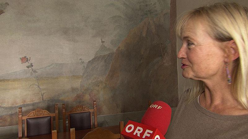 Imelda Krizan vor einer Wandmalerei in ihrem Haus