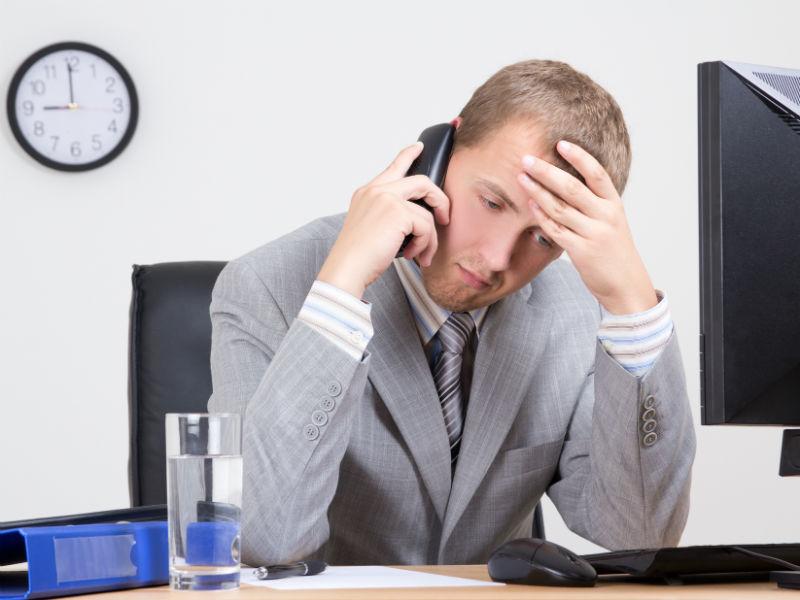 Mann telefoniert vor Computer