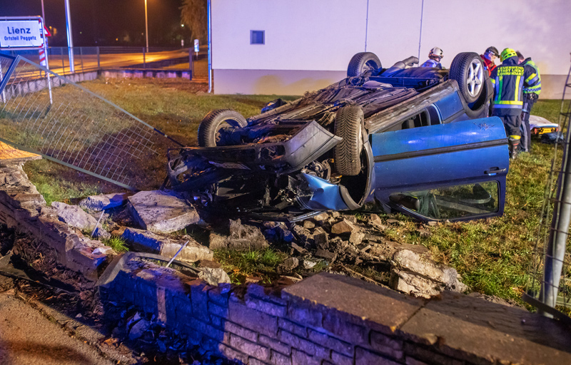 Auto liegt hinter Mauer auf Dach