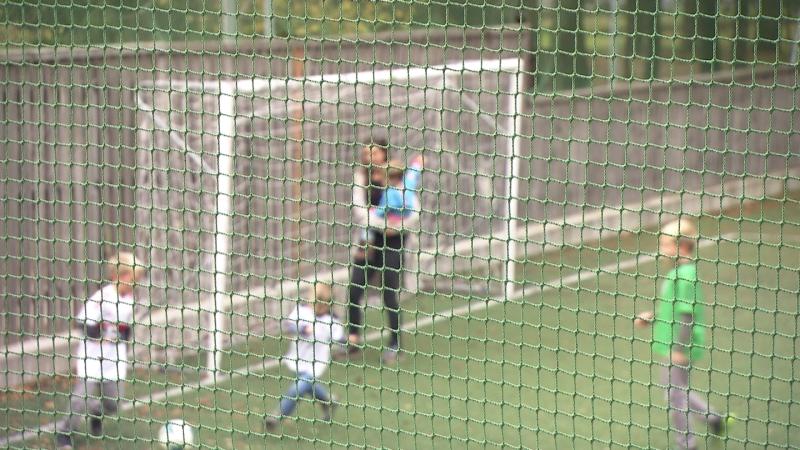 Mutter mit Kindern beim Fußballspielen auf Fußballfeld, alle unkenntlich