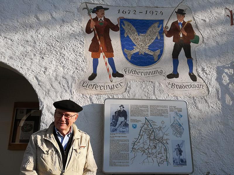 Werner Hölzl, Obmann des Lieferinger Kulturvereins vor dem Peter Pfenninger Haus mit Tafel des Lieferinger Kulturwanderwegs