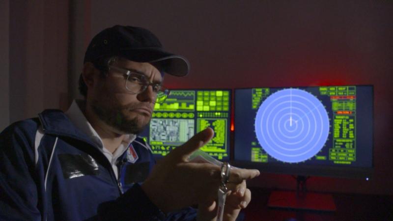 Patrick Rina mit Schildkappe vor einem Computer mit geheimnisvollen Buchstaben, als Komödie erkennbar