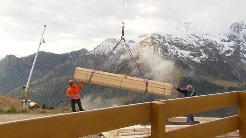 Hubschrauber liefert Holzbalken mittels Seilwinde an
