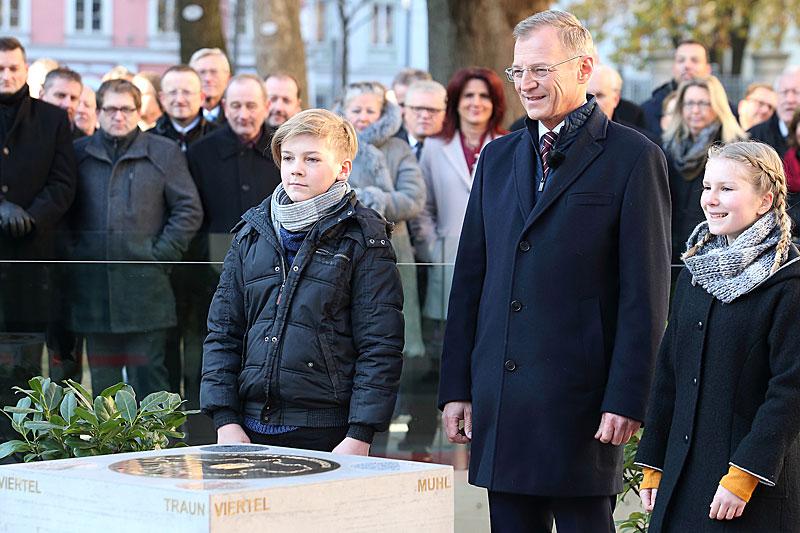 Landeshauptmann Thomas Stelzer mit den Kindern Rosalie Nova und Levin Börner vor dem Gedenkstein