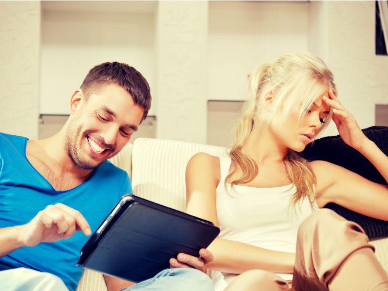 Mann lacht über tablet Frau schaut genervt