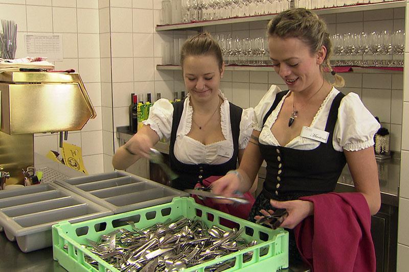 Junge Frauen im Dirndl polieren in Hotelküche das Besteck