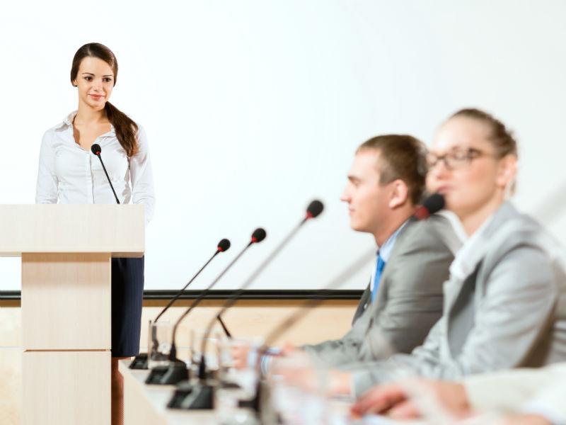 Frau steht vor Rednerpult