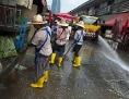 Arbeitsmigranten aus Myanmar reinigen eine Straße auf dem  Khlong Toei Markt in Bangkok, Thailand