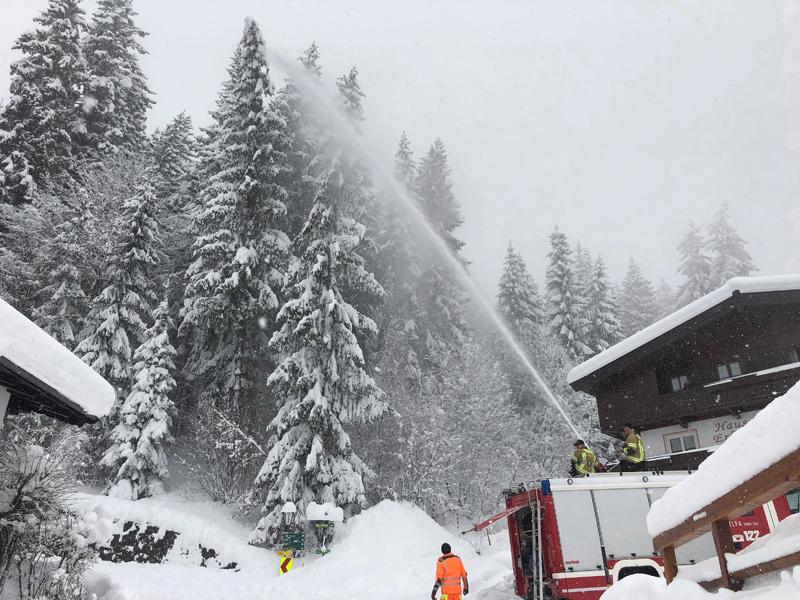 Feuerwehr spritzt Schnee von Bäumen
