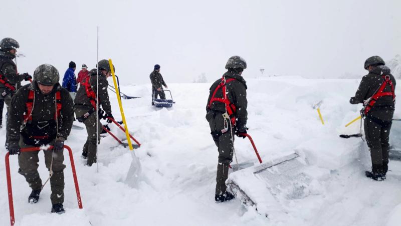 Soldaten räumen Schnee von Dach