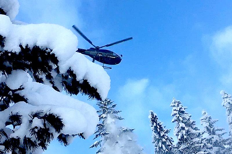 Hubschrauber über tief verschneiten Bäumen