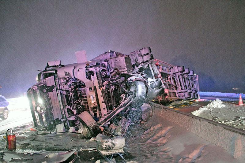 Wrack eines umgestürzten Lastwagens auf Autobahn im Schnee