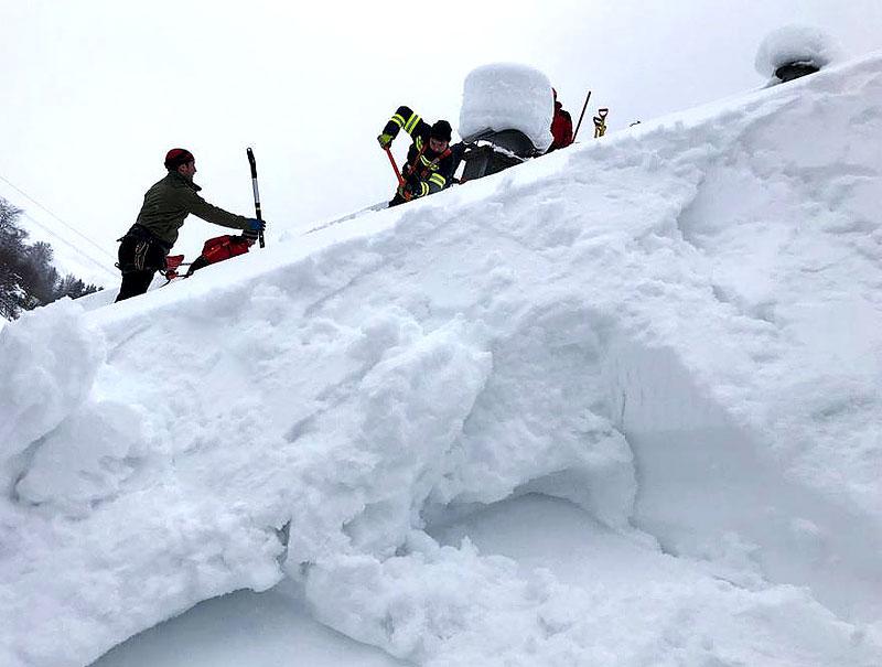 Schnee wird von Dächern geschaufelt
