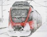 ÖBB Nahverkehrszug (Talent) im dichten Schneetreiben bei Bahnhof