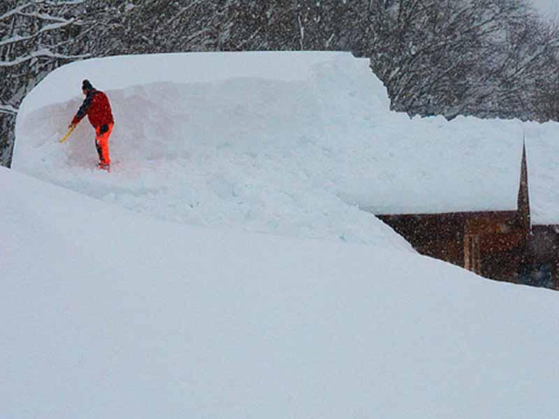 Dach wird von Schnee abgeschaufelt