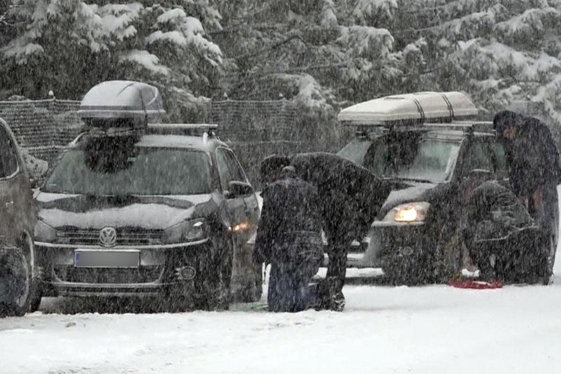 Urlauber legen Schneeketten bei Autos im Schneetreiben an