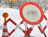 Scherengitter und Fahrverbotsschild auf Schneefahrbahn für Straßensperre / Lawinensperre