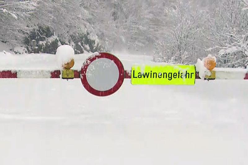 """Schranken und Straßensperre mit Schild """"Lawinengefahr"""" auf tief verschneiter Straße"""