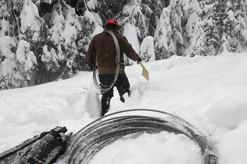 Techniker der Salzburg Netz GmbH im Schnee mit Draht für Stromleitungen