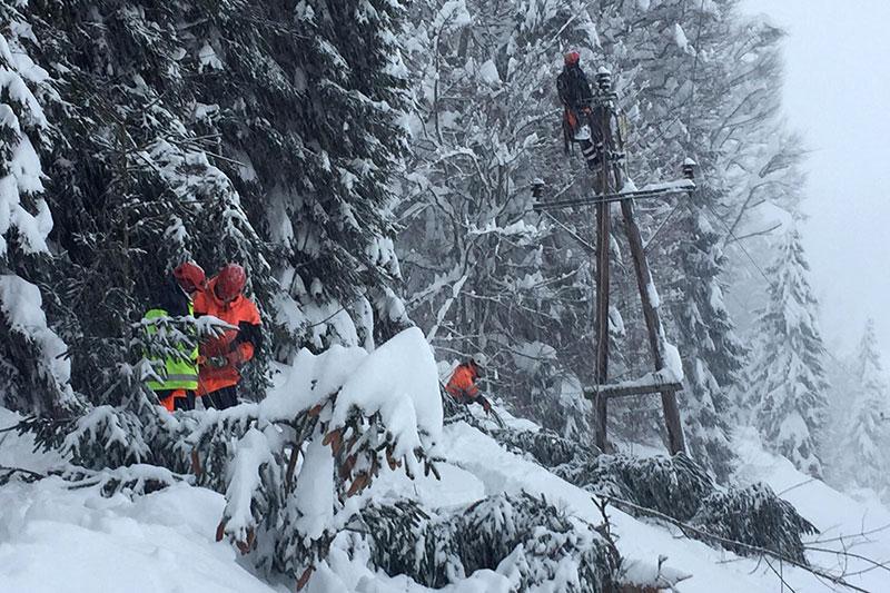 Techniker beim Wiederherstellen einer Stromleitung im dichten Schneefall