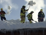 Feuerwehrleute schaufeln verschneites Hausdach ab