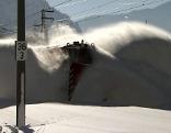 Schneepfluglokomotive der ÖBB beim Räumen von Bahnstrecke bei Sonnenschein (im Pongau)