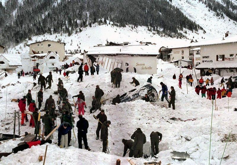 Rettungsmannschaftem suchen unter Trümmern und Schnee nach Verschütteten