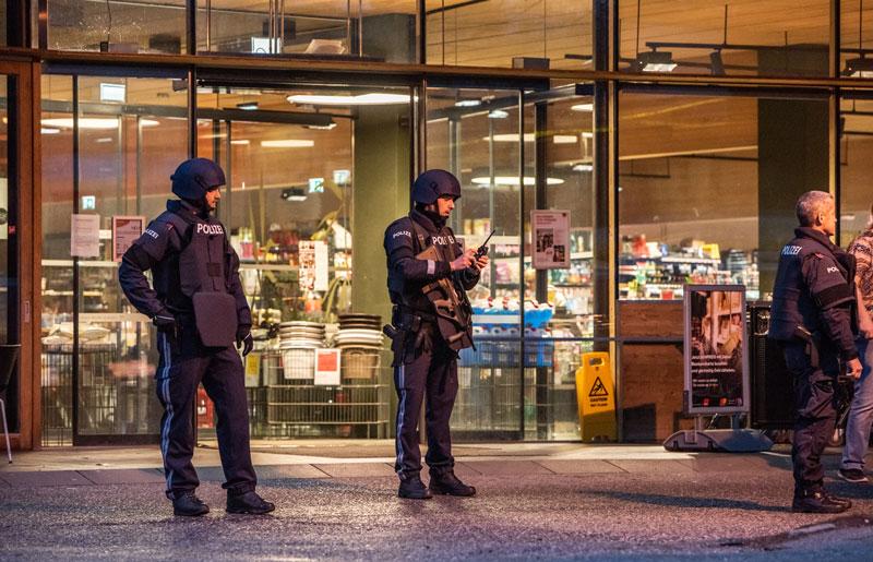 Zwei Polizisten vor dem Eingang des überfallenen Supermarktes