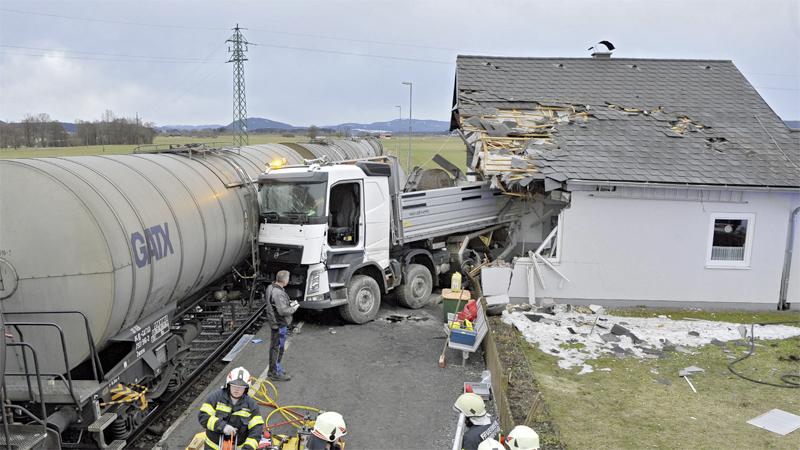 Lkw von Zug in Haus geschleudert