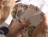 Alter Mann hält Spielkarten